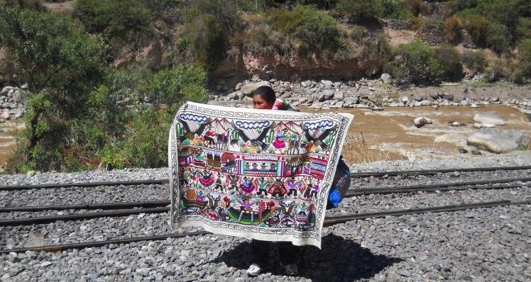 Vendendo artigos típicos enquanto o trem para em Ollantaytambo